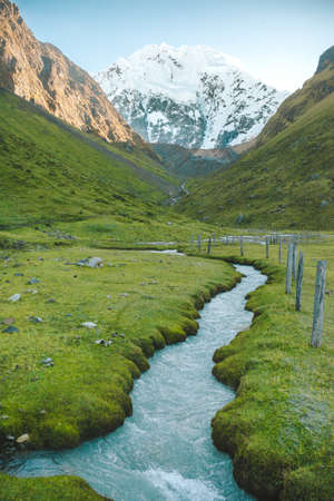 salkantay: Salkantay Mountain looms in the distance above a glacial river in Peru.