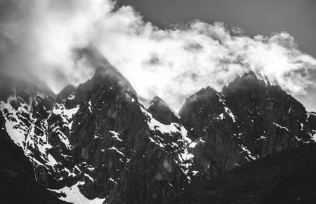 stark: Sharp mountain peaks cut though the sunlight as it hits the clouds, casting stark shadows - Peru