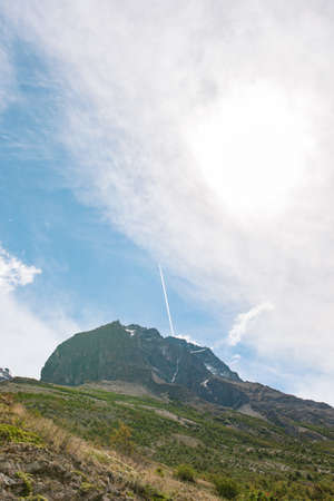 torres del paine: A jet soars above Torres del Paine National Park leaving behind a straight, clear contrail - Chile