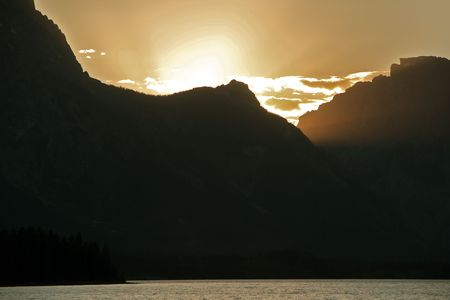 A beautiful sunset behind the Grand Tetons over Jackson Lake Фото со стока