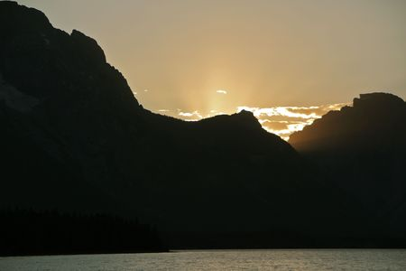 A sunset behind the Grand Tetons over Jackson Lake