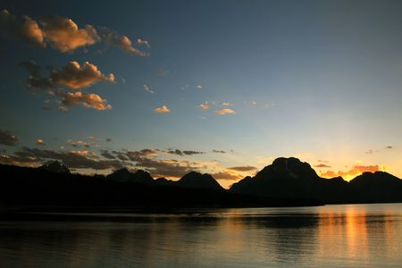 A beautiful sunset over the Grand Tetons and Jackson Lake Фото со стока