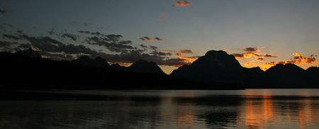 A beautiful sunset over Jackson Lake and the Grand Tetons Фото со стока