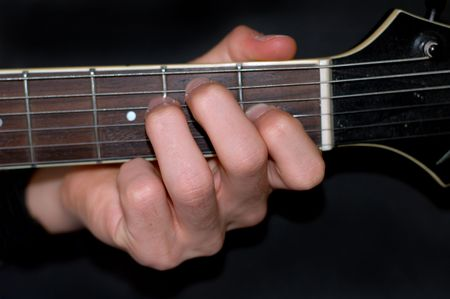 Man holding an E chord on an electric guitar photo