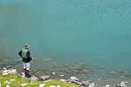 Fly fisherman on a lake (Alp) photo