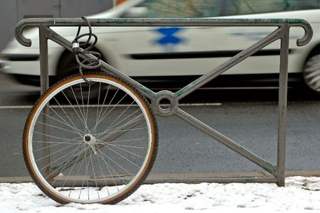 velocipede: Bicycle wheel locked alone to a gate. In the background, an ambulance.