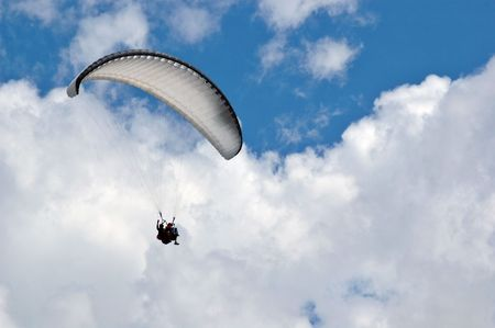 paragliding baptism with an instructor in a cloudy sky photo