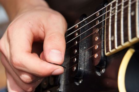 Right hand picks electric guitar strings on a black guitar Stock Photo