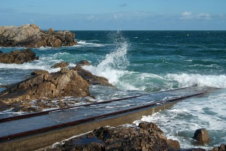 slipway: Slipway and waves breaking on the rocky coast of Normandy (France) Stock Photo