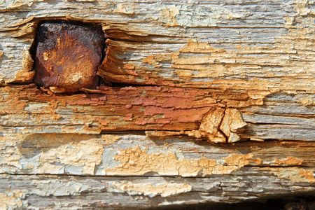 flaking: Some old painted and rusty boards in a boat cemetary with a large nail