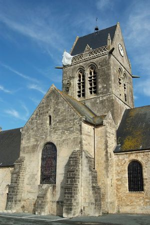 mere: Sainte-Mère-Eglise was the first town liberated by the Allies just before H-Hour on D-Day.  The town was the scene of a famous incident where American paratrooper John Steele had his parachute caught on the spire of the church. There is a dummy and parach