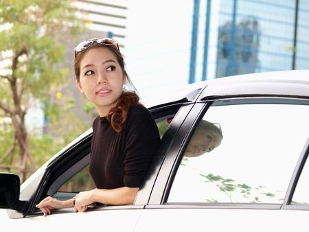 Jonge mooie Aziatische meisje op zoek naar achterkant van de auto Stockfoto
