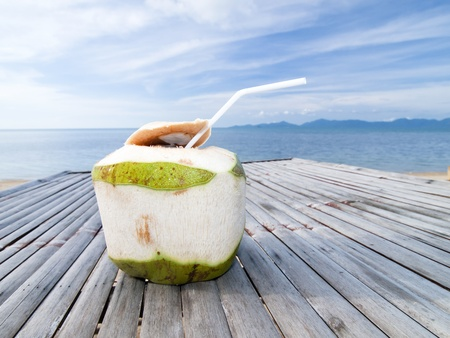 Coconut Water Drink on bamboo table with sea background photo