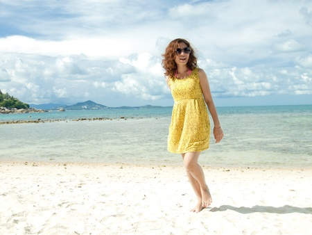 Asian Women happy on the Beach with vibrant yellow dress photo