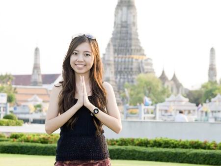 Aantrekkelijke Aziatische vrouw begroeting met Tempel van de Dageraad Wat Arun achtergrond