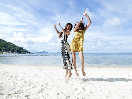 woman jumping together on sand beach with blue sky background Stock Photo