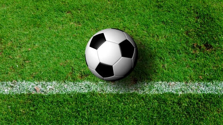 Soccer Ball on green grass field from top view photo