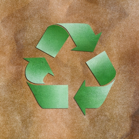 Grunge paper texture green recycle sign on brown background photo
