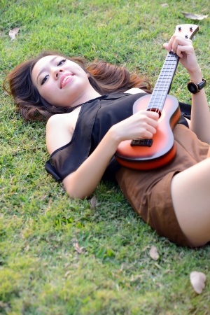 Asia women playing Ukulele in park outdoor  photo