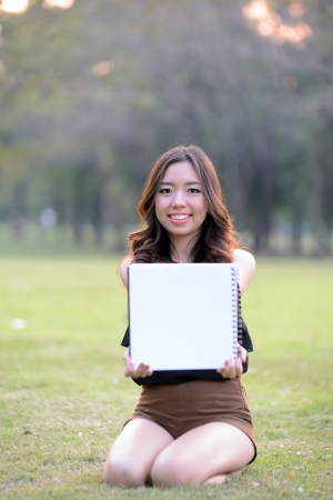 Asia woman show blank paper in the park photo