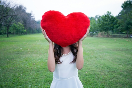 Women holding big love heart shape pillow in the park