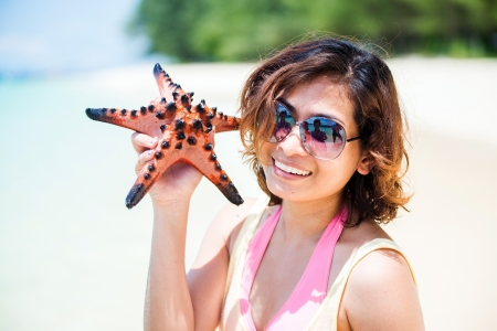 Young woman shows starfish during holiday at tropical island photo