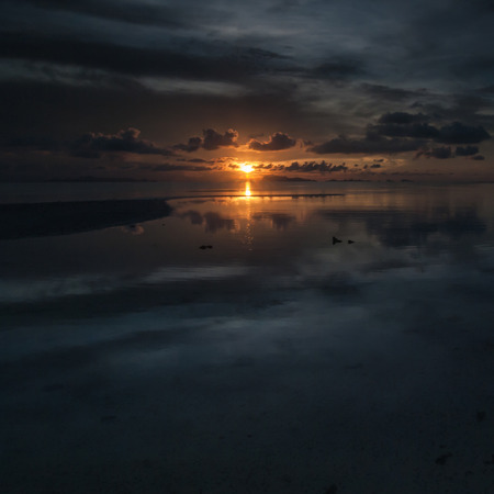 The sun sets over beach with beautiful reflection photo