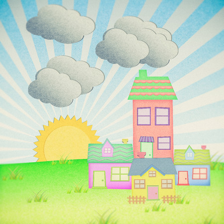 house from recycle paper with grass field and sun set background Stock Photo