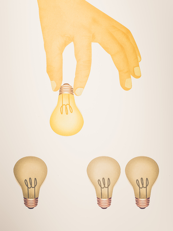 Paper texture ,  illustration of hand picking bright light bulb Stock Photo