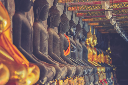 veneration: golden buddhas lined up along the wall of buddhist temple (Vintage filter effect used) Stock Photo
