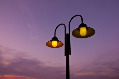 The light of a street lamp near the sea at sunset photo