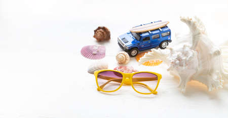 Yellow sunglasses and shells on a white wooden floor