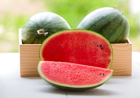 Watermelon cut into pieces on a wooden cutting board placed on the table