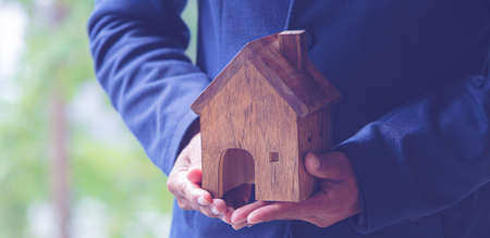 The hands of the businessmen holding the house model