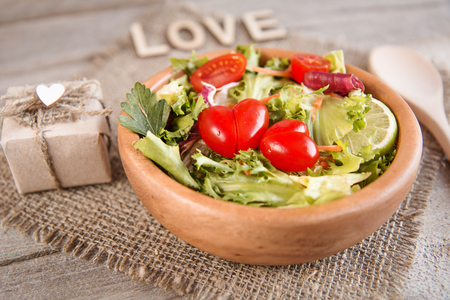 salad of organic vegetables for a loved one in a wooden dish on a wooden table Stock Photo