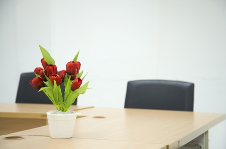 Two black chairs in a meeting room with Red flower on Meeting room tablet  Stock Photo