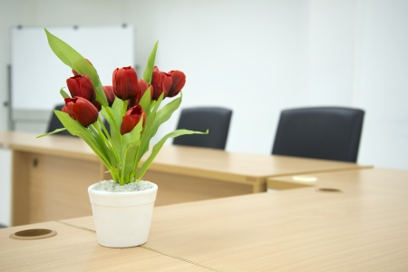 Two black chairs in a meeting room with Red flower on Meeting room tablet and white board in the background Stock Photo