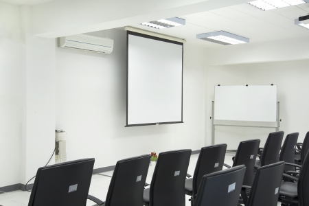 An Empty conference room with blackchairs ,Projection screen and whiteboard photo
