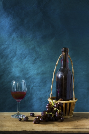 Still life Photography with Old red wine on wooden table and blue grunge background Stock Photo