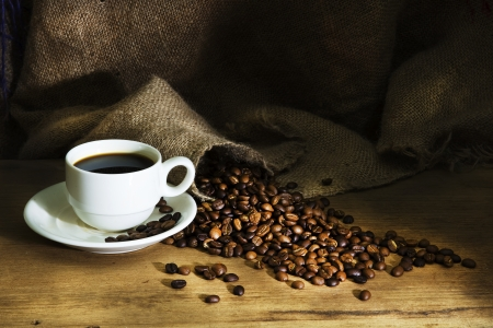 Coffee cup and coffee beans on a wooden table and sack background