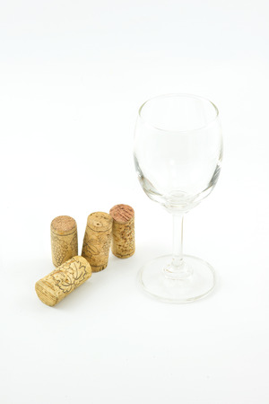 staggered:  vintage wine corks and wineglass on white background.