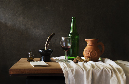 Still life Photography with  red wine on wooden table and note photo