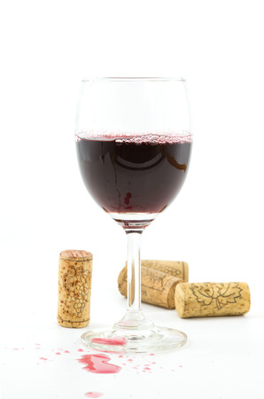 staggered:  vintage wine corks,red wine in wineglass on white background. Stock Photo