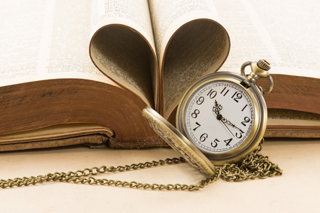 Vintage  antique pocket watch and heart of the books pages photo