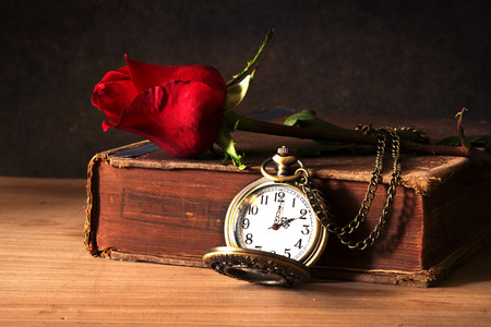 Still life with Red rose on the old  book in the dark and heart photo