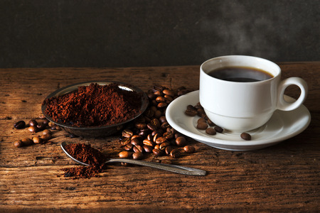 Still life with Hot Coffee in  cup and coffee beans,ground coffee on a wooden table.