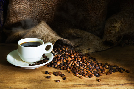 Hot Coffee cup and roast coffee beans on a wooden table and sack background Stock Photo
