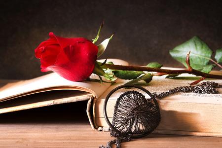 Nature morte avec une rose rouge sur le livre ouvert et le c?ur dans l'obscurité, Saint Valentin, l'amour