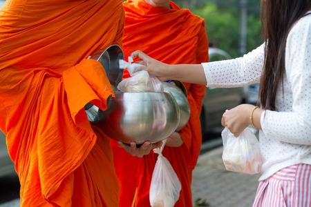 limosna: Los budistas tienen fe en el budismo. dar limosna a los monjes recibir limosnas