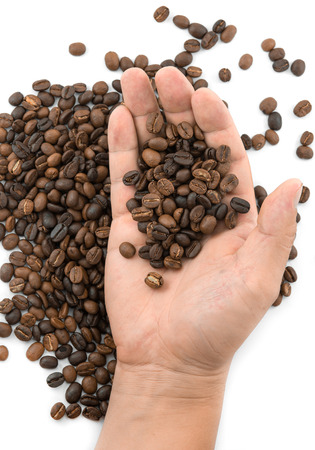 manos: Fresh roasted coffee beans pouring out of male hands Stock Photo